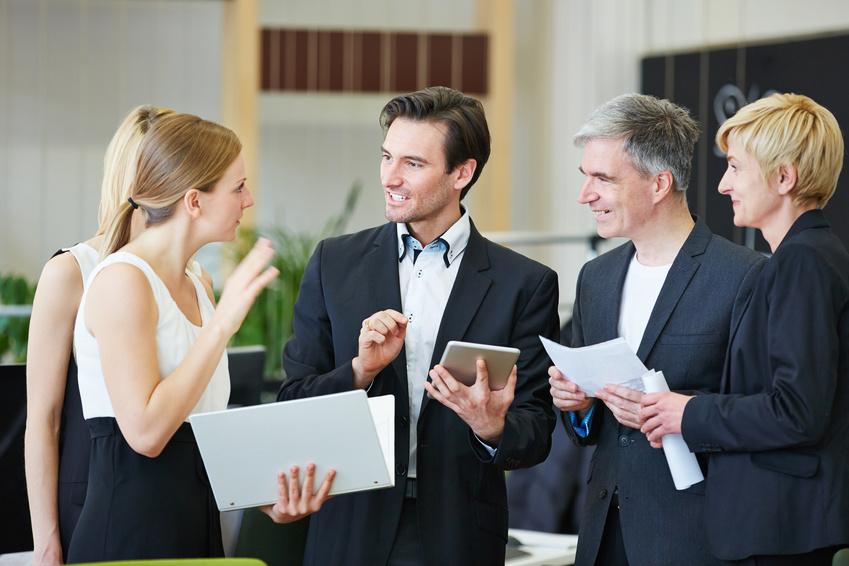 Mehrere Geschäftsleute diskutieren im Büro zusammen als Team über eine Entscheidung